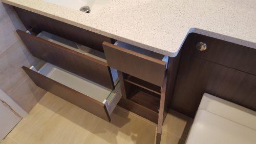 Brown bathroom units with light worktop