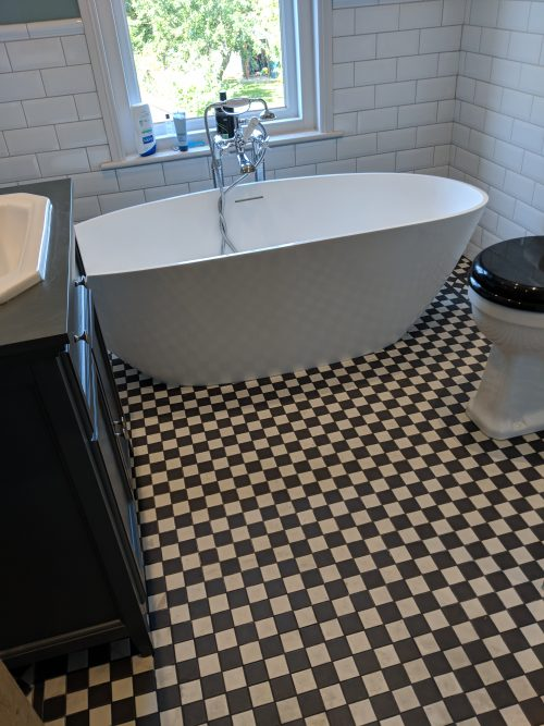 Floor standing white oval bath and chequered floor tiles