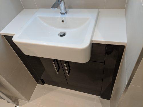 Stunning glossy finish dark unit and light tiling and basin.