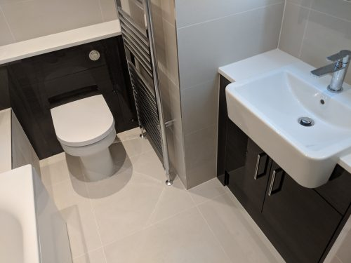Stunning glossy finish dark unit and light tiling, wc and basin.