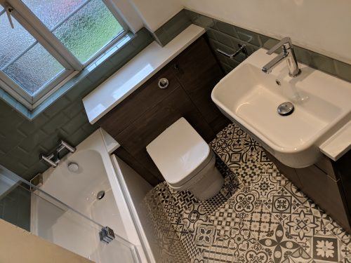 Lovely floor tiles with white bath sink and basin, and dark units