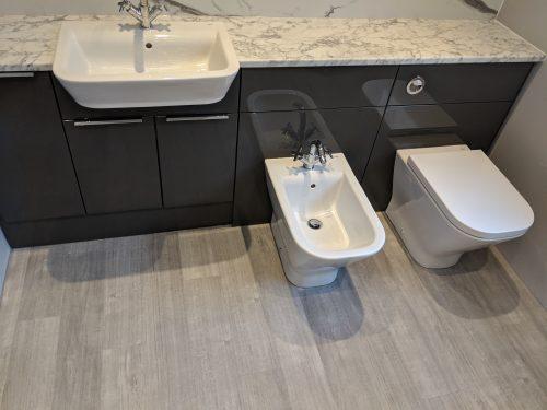 Dark units with marbled worktop, bidet and toilet