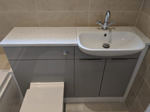 Renovated bathroom with grey units